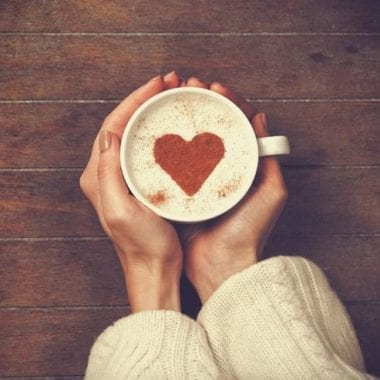 A woman holds a mug with a heart in her latte | PCRM Fertility Clinic Vancouver