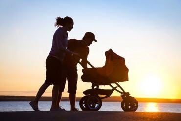 Two parents push a baby in a stroller during sunset | PCRM Fertility Clinic Vancouver