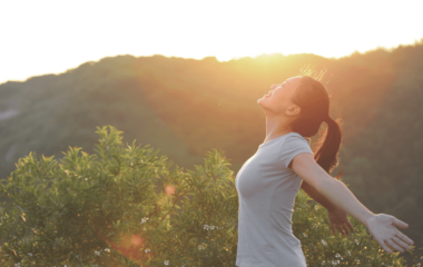 Woman stretches out her hands in the outdoors - feeling the freedom and relief of assisted reproduction | PCRM Fertility Clinic Vancouver