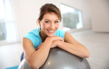 A woman smiles while resting on a yoga ball after receiving tubal ligation reversal at PCRM | PCRM Fertility Clinic Vancouver