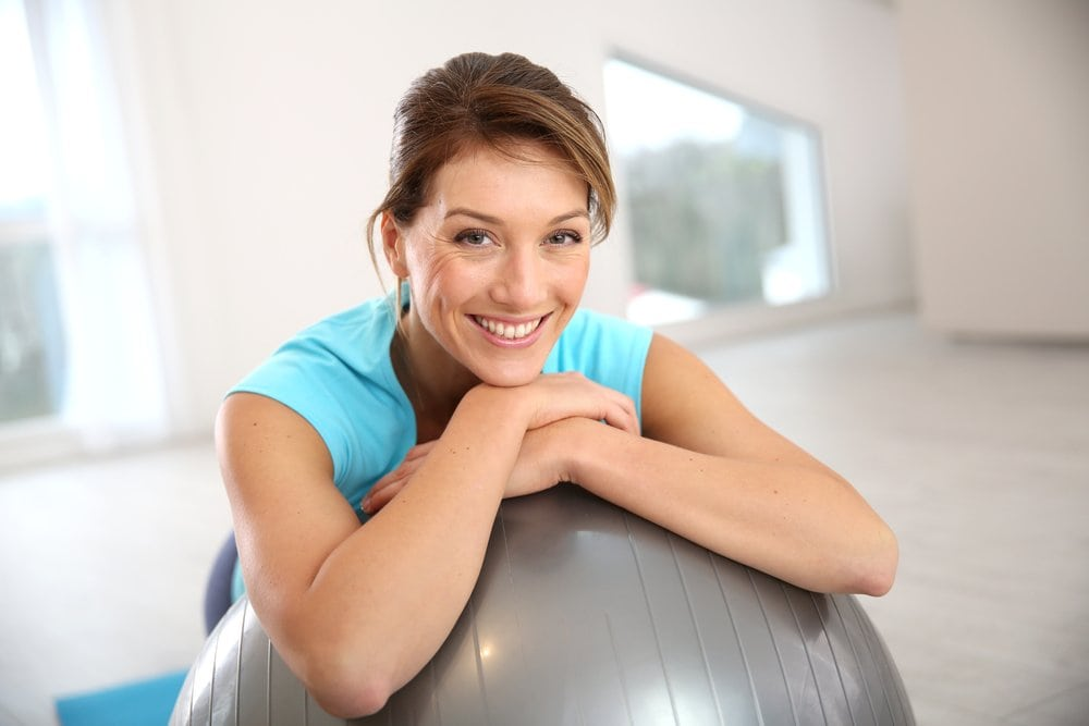 Woman smiles casually on yoga ball in studio after fertility treatment