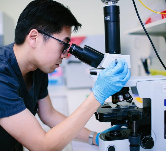 A fertility specialist performs fertility research with a microscope | PCRM Fertility Clinic Vancouver