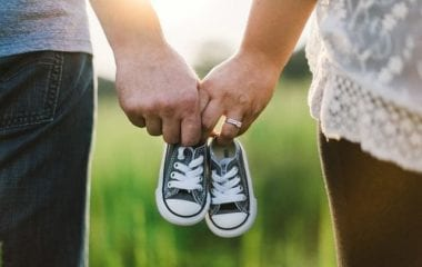 surrogacy couple holding baby shoes | PCRM Fertility Clinic in Vancouver