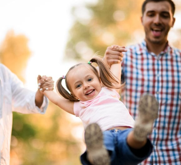 Parents playing with their toddler daughter in a park | PCRM Fertility Clinic Vancouver